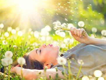 Frau liegt auf der Wiese mit Pusteblume