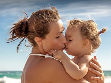 Frau mit Säugling im Arm am Meer